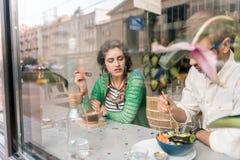 Couples affectueux mignons prenant le petit déjeuner ensemble dans le cafétéria confortable de vegan photo libre de droits