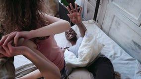 Couples affectueux multi-ethniques sur le lit, combat par des oreillers Femme et homme dans des pyjamas passant des loisirs à la  photographie stock
