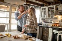 Couples affectueux préparant des pâtes dans la cuisine photographie stock