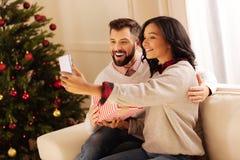 Couples affectueux prenant des selfies le réveillon de Noël Photos stock