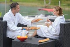 Couples affectueux prenant le petit déjeuner au lac dehors Photographie stock
