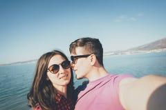 Couples affectueux prenant le selfie sur le fond de la mer Image libre de droits