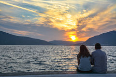 Couples affectueux regardant le coucher du soleil sur le bord de mer Images libres de droits