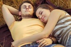 Couples affectueux se couchant sur le champ floral en parc automnal, chaud Image stock