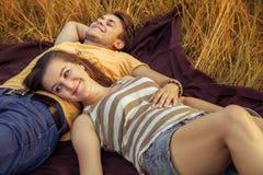 Couples affectueux se couchant sur le champ floral en parc automnal, chaud Photo stock