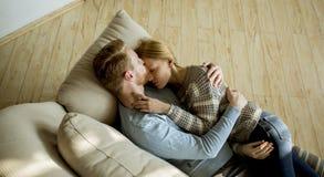 Couples affectueux se couchant sur le sofa dans la chambre photo libre de droits