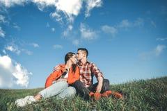 Couples affectueux se reposant dans les caresses sur l'herbe Photographie stock