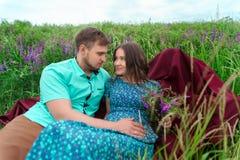 Couples affectueux se reposant ensemble au milieu des fleurs sur un pré honeymoon Image stock