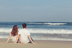 Couples affectueux se reposant sur la plage au temps de jour Photos stock