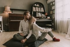 Couples affectueux se reposant sur le plancher dans la chambre Photographie stock