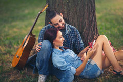 Couples affectueux se tenant s'asseyant sur un tronc d'arbre Images libres de droits