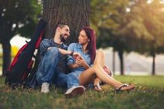 Couples affectueux se tenant s'asseyant sur un tronc d'arbre Photographie stock libre de droits