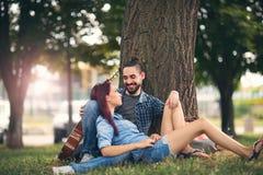 Couples affectueux se tenant s'asseyant sur un tronc d'arbre Photo libre de droits