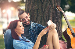 Couples affectueux se tenant s'asseyant sur un tronc d'arbre Photo stock