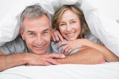 Couples affectueux sous la couette photos stock