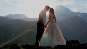 Couples affectueux sur le fond du coucher de soleil, montagnes banque de vidéos