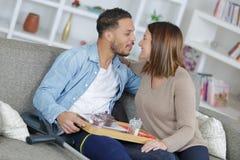 Couples affectueux sur le husaband blessé par sofa Photographie stock libre de droits
