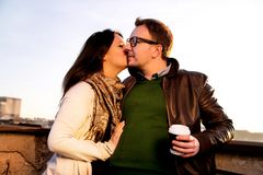 Couples affectueux sur le toit, fille embrassant le jeune homme Images stock
