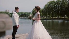 Couples affectueux sur un quai La belle jeune mariée montre sa robe de mariage, tourbillonne autour Le rire heureux d'amants et a clips vidéos