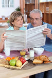 Couples affichant le journal Images stock