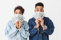 Couples africains étonnés dans des chemises de denim couvrant leurs visages Photo stock