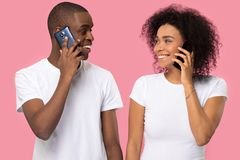 Couples africains attrayants tenant des t?l?phones regardant l'un l'autre images stock