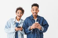 Couples africains heureux étonnés dans des chemises de denim tenant leurs smartphones Photos stock