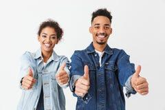 Couples africains heureux dans des chemises de denim montrant des pouces  Image libre de droits