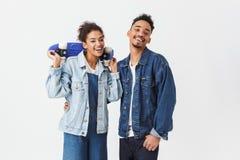 Couples africains heureux dans des chemises de denim posant ensemble Images stock