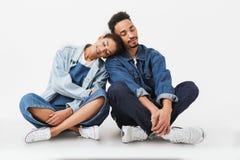 Couples africains heureux dans des chemises de denim se reposant ensemble sur le plancher Image libre de droits