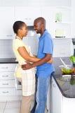 Couples africains intimes dans la cuisine Image stock