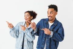 Couples africains joyeux dans des chemises de denim se dirigeant avec des index Photos stock