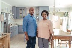 Couples africains mûrs de sourire se tenant ensemble dans leur cuisine Images stock