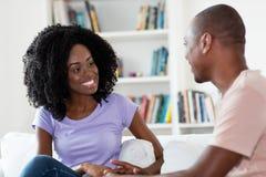 Couples africains parlant et flirtant à la maison images stock