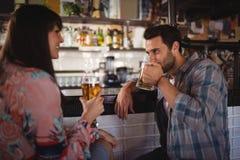 Couples agissant l'un sur l'autre tout en ayant la bière au compteur Photos libres de droits