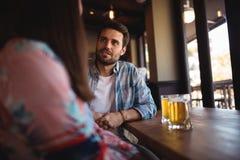 Couples agissant l'un sur l'autre tout en ayant la bière au compteur Photo stock