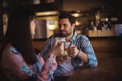 Couples agissant l'un sur l'autre tout en ayant la bière au compteur Images stock