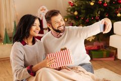 Couples agréables prenant le selfie avec le cadeau de Noël Images stock