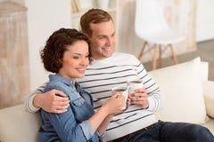 Couples agréables se reposant sur le divan Images libres de droits