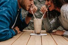 Couples aimants partageant le milkshake image stock