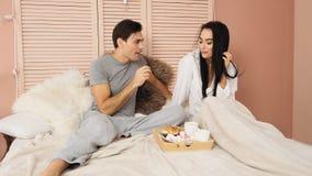 Couples aimants prenant le petit déjeuner dans le lit de l'hôtel et de s'alimenter Mouvement lent clips vidéos