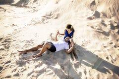 Couples aimants sur la plage dans étreindre de sable Le concept de l'amour et une date en mer image libre de droits
