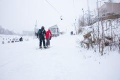 Couples allant colline pour le ski Photos stock