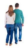 Couples allants de vue arrière fille et type amicaux de marche tenant h Images stock