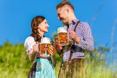 Couples allemands dans Tracht avec de la bière, bretzel Image libre de droits