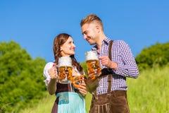 Couples allemands dans Tracht avec de la bière et le bretzel Photo libre de droits