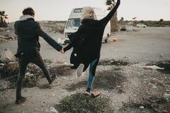 Couples alternatifs tenant des mains et le fonctionnement vers leur fourgon avec l'excitation photo stock