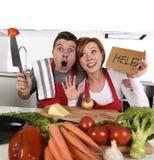 Couples américains dans la cuisine d'effort à la maison en faisant cuire le tablier demandant l'aide frustrée Photographie stock