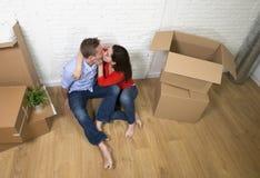 Couples américains heureux se reposant sur le plancher embrassant célébrant le déplacement en appartement ou appartement de nouve Image stock