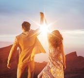 Couples ambitieux regardant le coucher du soleil avec un geste victorieux Image libre de droits